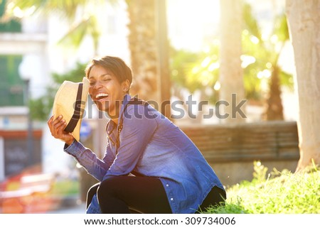 Side portrait of a carefree young woman laughing outside - stock photo