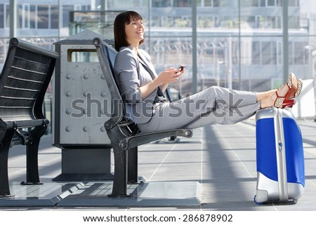 Side portrait of a happy business woman smiling with bag and mobile phone - stock photo