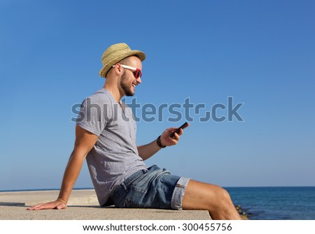 Side portrait of a happy young man sitting by the sea with mobile phone - stock photo