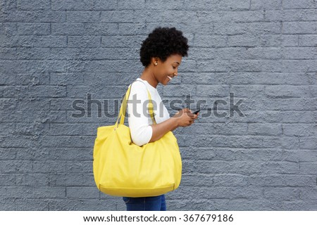 Side portrait of a happy young woman with a bag reading text message on her mobile phone - stock photo