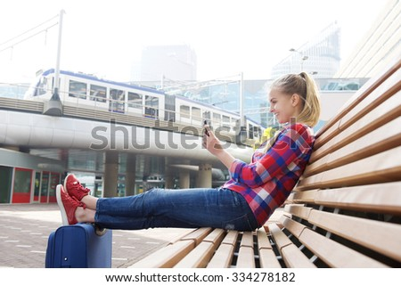 Side portrait of a smiling travel woman sitting outside with mobile phone - stock photo