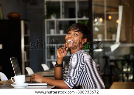 Side portrait of a smiling young african american woman sitting at cafe with laptop - stock photo
