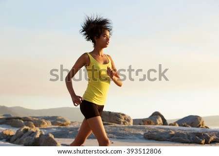 Side portrait of a young african american woman speed walking outdoors - stock photo