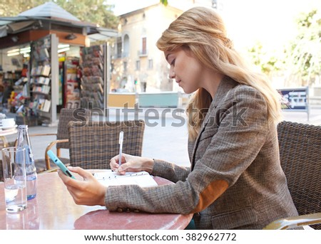 Side portrait of a young business woman using a smart phone and taking notes, working in a coffee shop terrace in a classic city, outdoors. Professional businesswoman using technology, sunny exterior. - stock photo