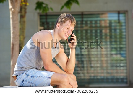 Side portrait of a young man smiling and listening to mobile phone call