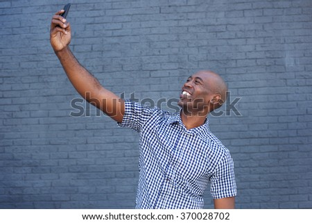 Side portrait of an african american man taking a selfie with mobile phone  - stock photo