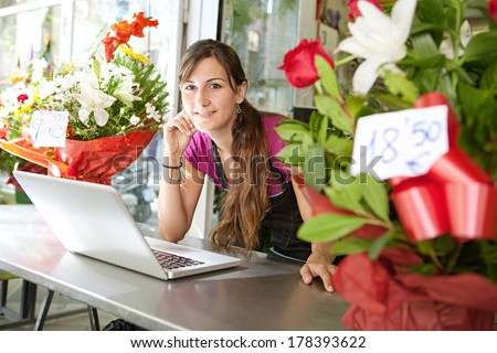 Side portrait of an attractive florist business woman owner at a flower shop counter using a laptop computer to place a stock order on line, smiling. Small business technology. - stock photo