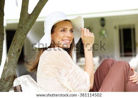 Side portrait of an attractive woman smiling with sun hat - stock photo