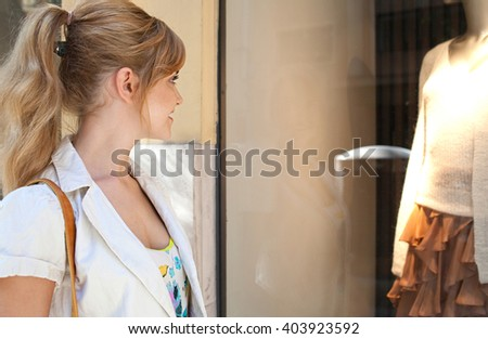 Side portrait of beautiful young woman in a city shopping street looking at fashion store window, smiling outdoors. Fashionable consumer girl spending money on holiday, travel lifestyle, exterior. - stock photo