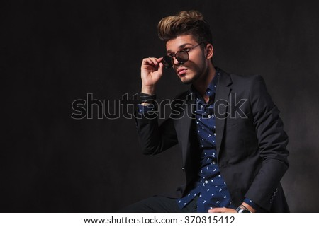 side portrait of fashionable young man posing in dark studio background while seated. he is taking off his sunglasses.  - stock photo