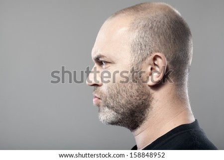 side portrait of gloomy man isolated on gray background with copyspace - stock photo