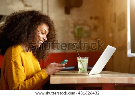 Side portrait of happy young african woman in a coffee shop using mobile phone - stock photo