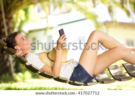 Side portrait of happy young woman lying on a hammock outdoors and listening to music on her mobile phone - stock photo