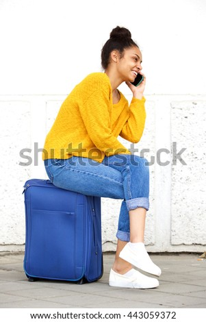 Side portrait of happy young woman sitting outside on suitcase and talking on cellphone - stock photo