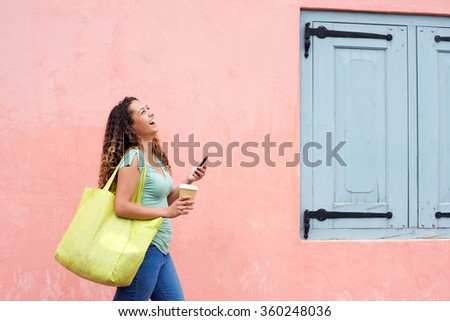 Side portrait of laughing woman walking with mobile phone and bag - stock photo