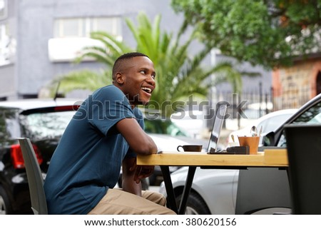 Side portrait of young african man sitting at outdoor coffee shop with a laptop   - stock photo