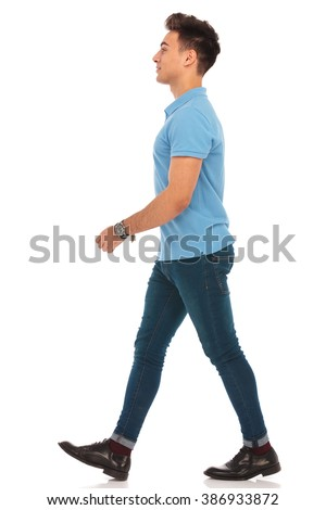 side portrait of young man in blue shirt walking in isolated studio background, looking away from the camera - stock photo