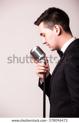 Side portrait of young man in suit singing with the microphone. Isolated on grey background. Singer concept. - stock photo