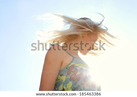 Side portrait view of a joyful happy blond woman throwing her hair flying in the air against the sun shining rays filtering with flare in a spontaneous celebratory expression. Healthy lifestyle. - stock photo