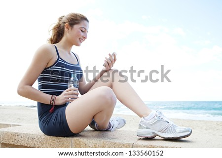 "Side portrait view of a young attractive woman having a break from exercising and holding a bottle of mineral water and using a ""smart phone"", smiling."