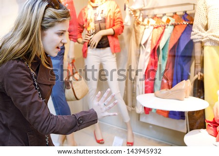 Side portrait view of a young teenager girl looking at the clothes in a fashion store shop window, with a surprise expression and leaning on the window.