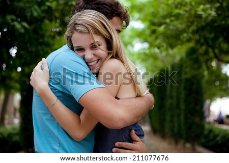Side portrait view of a young tourist couple in love, embracing with joyful expressions while visiting a romantic green park on holiday, traveling. Lovers outdoors lifestyle. - stock photo
