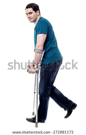 Side pose casual man walking with crutches