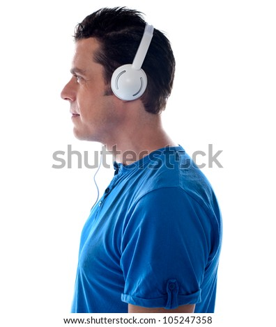 Side pose of a man with headphones. Tuned into music