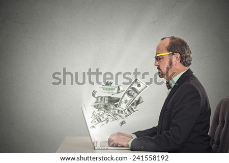 Side profile corporate business man with glasses working online on computer earning money dollar bills banknotes flying out of laptop screen isolated grey wall office background. Human face expression - stock photo