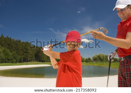 Side profile of a boy swinging a golf club with his father standing beside him - stock photo