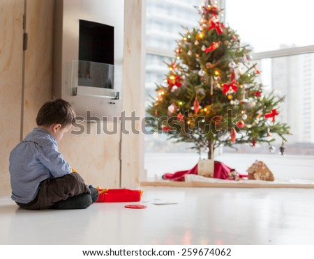 Side profile of a little boy playing with toy car and Christmas tree in the background - stock photo