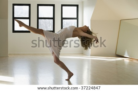Side profile of a mid adult woman dancing with leg extension