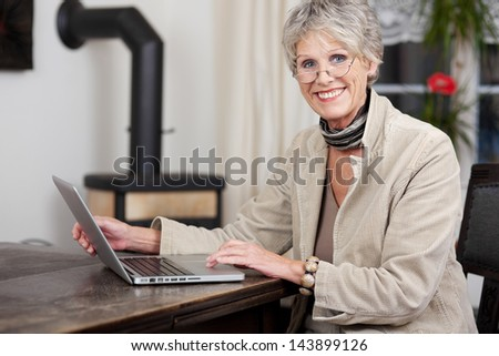 Side profile of a senior female smiling while working on her laptop. - stock photo