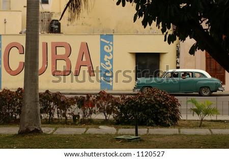 Side profile of a vintage car on an empty street, Havana, Cuba - stock photo