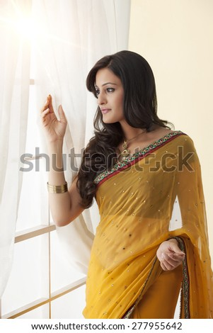Side profile of a woman in a saree looking out a window - stock photo