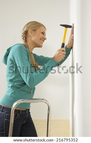 Side profile of a young woman hammering a nail into a wall - stock photo