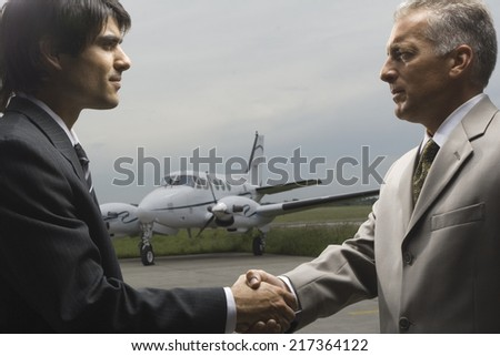 Side profile of two businessmen shaking hands - stock photo