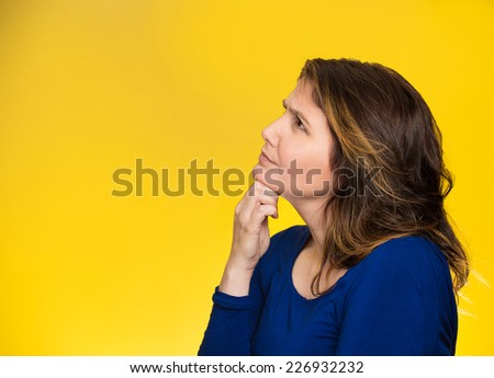 Side profile portrait happy beautiful woman thinking looking up isolated yellow background with copy space. Human face expressions, emotions, feelings, body language, perception - stock photo