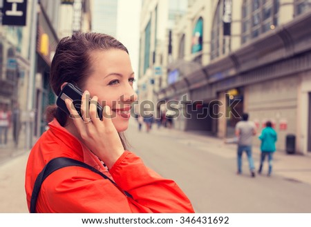Side profile portrait happy young lady attractive woman talking on mobile phone outdoors - stock photo