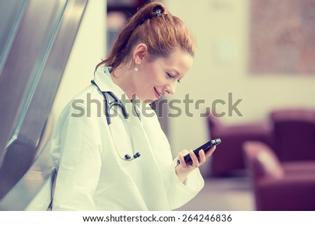 Side profile portrait smiling female doctor, healthcare professional in white lab coat with stethoscope, analyzing data results on mobile smart phone standing in hospital hallway corridor  - stock photo