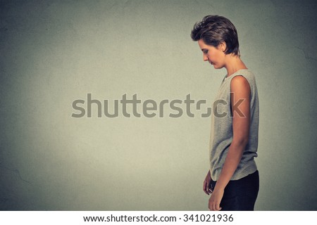 Side profile sad lonely young woman standing looking down isolated on gray wall background