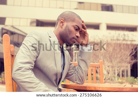 side profile stressed young businessman sitting outside corporate office holding head with hands looking down. Negative human emotion facial expression feelings. - stock photo