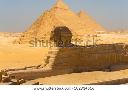 Side profile view of the Great Sphinx with all of the pyramids of Giza in the background in Cairo, Egypt on a clear sunny, blue sky day. Horizontal - stock photo