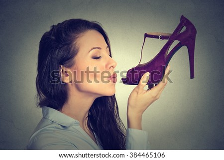 Side profile woman kissing shoe. Women loves high heel shoes concept. Beautiful young happy female model isolated on gray wall background  - stock photo