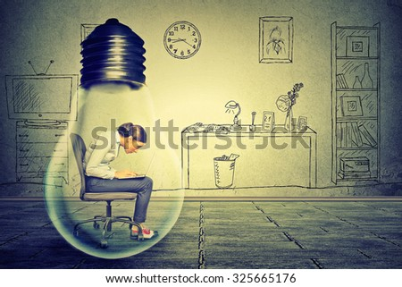 Side profile young woman using working on computer sitting inside electric lamp in her corporate office on a gray wall background. Generate idea concept