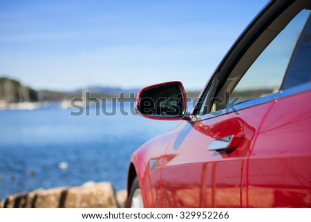 side rear-view mirror on a modern red car - stock photo