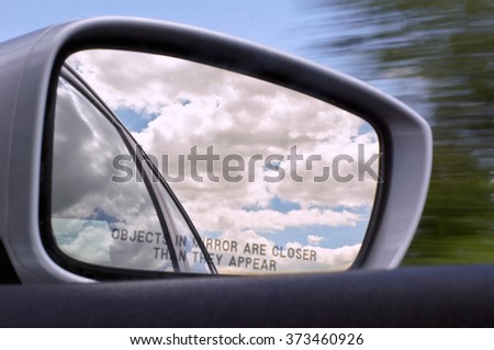 Side Rear-View Mirror. Reflections of fluffy clouds with rural scenery & motion blur in the background. - stock photo