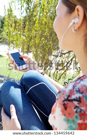"Side rear view of a young woman in a park holding a ""smart phone"" with a black screen and listening to music with her earphones."