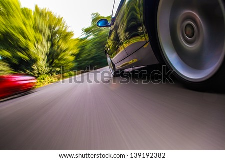 Side rear view of black car driving fast.