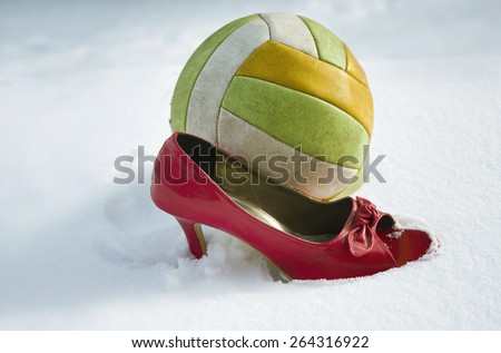 Side shot of a football ball and red high heel on the snow, concept of sport and fashion - stock photo